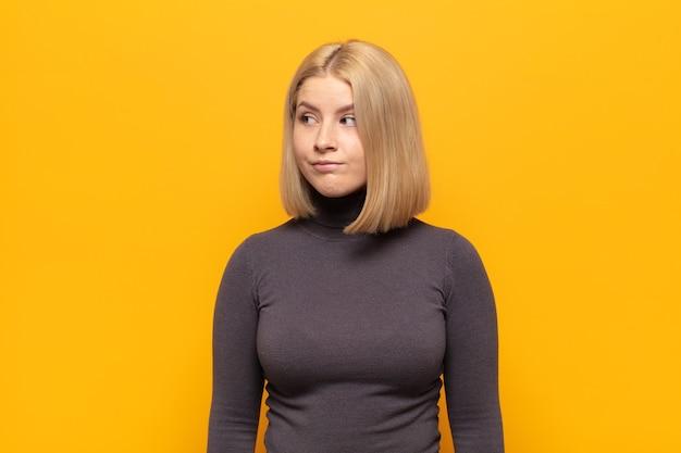 Blondynka wyglądająca na zaskoczoną i zdezorientowaną, zastanawiająca się lub próbująca rozwiązać problem lub myśląca