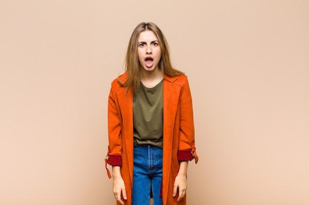 Blondynka wyglądająca na zszokowaną, wściekłą, zirytowaną lub rozczarowaną, z otwartymi ustami i wściekłą