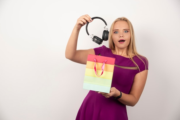 Blondynka wyjmując słuchawki z torby z szczęśliwym wyrazem twarzy.
