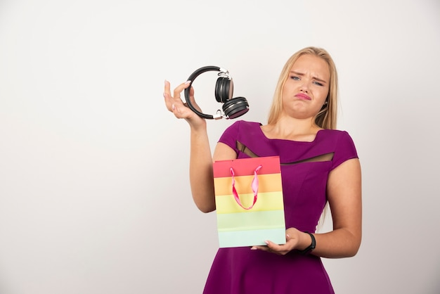 Blondynka wyjmując słuchawki z worka.