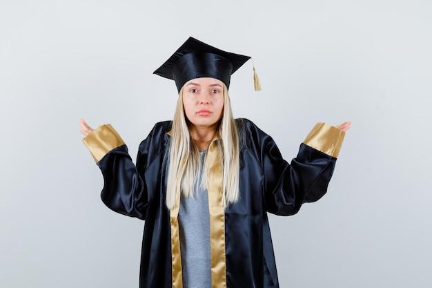 Blondynka wzrusza ramionami w sukni i czapce ukończenia szkoły i wygląda na zakłopotaną.