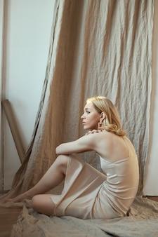 Blondynka z biżuterią w uszach siedzi przy oknie w promieniach wieczornego słońca.