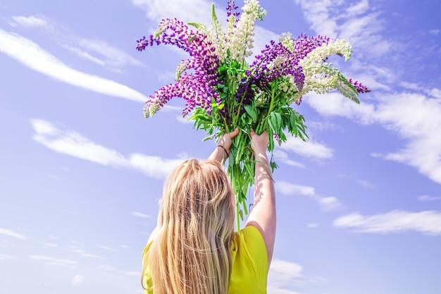 Blondynka z bukietem łubinów na tle błękitnego nieba. letni słoneczny dzień.