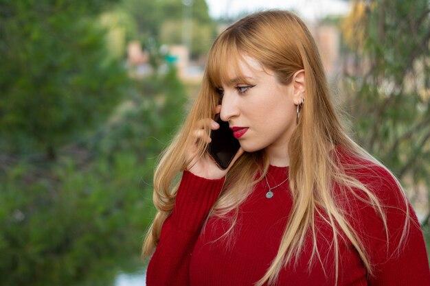Blondynka z czerwoną szminką i czerwonym swetrem rozmawia jej telefon komórkowy.