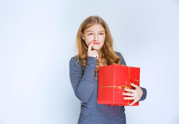 Blondynka z czerwonym pudełkiem wygląda na zamyśloną i zmęczoną.