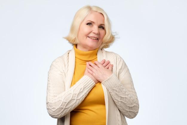 Blondynka z delikatnym uśmiechem, trzyma obie dłonie na piersi