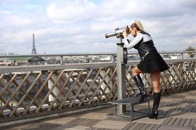 Blondynka z długimi nogami w krótkiej spódniczce patrzy przez teleskop na wieżę eiffla