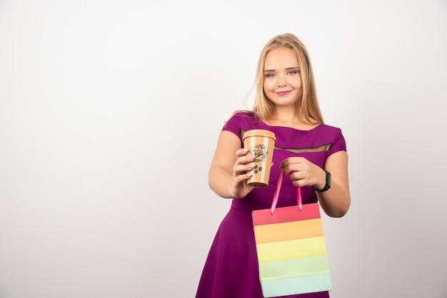 Blondynka z filiżanką kawy i torbę pozowanie.