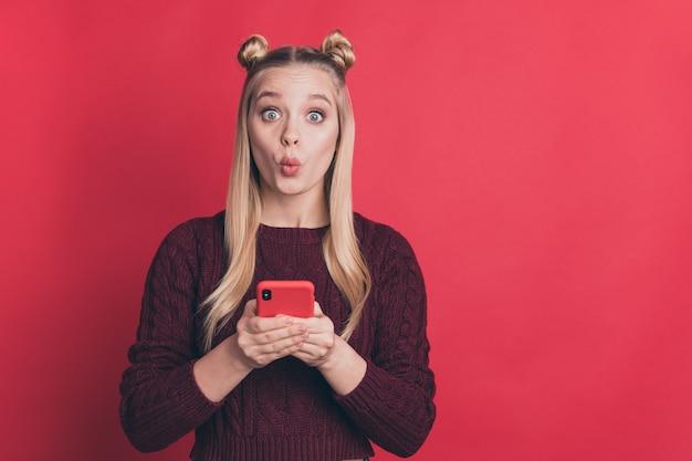 Blondynka z górnymi węzłami pozuje z jej telefonem na czerwonej ścianie