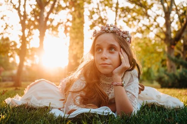 Blondynka z kręconymi włosami ubrana w sukienkę komunijną leżącą na trawie do zdjęć