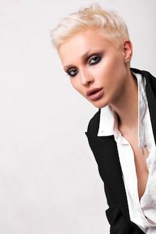 Blondynka z krótkimi włosami i zadymionym lodem na białym tle w studio.