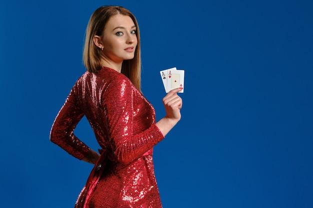 Blondynka z makijażem w czerwonej cekinowej sukience pokazuje dwa asy pozujące bokiem na niebieskim tle...