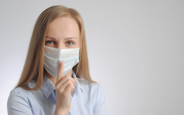 Blondynka z maską medyczną pokazuje gest ciszy i spokoju