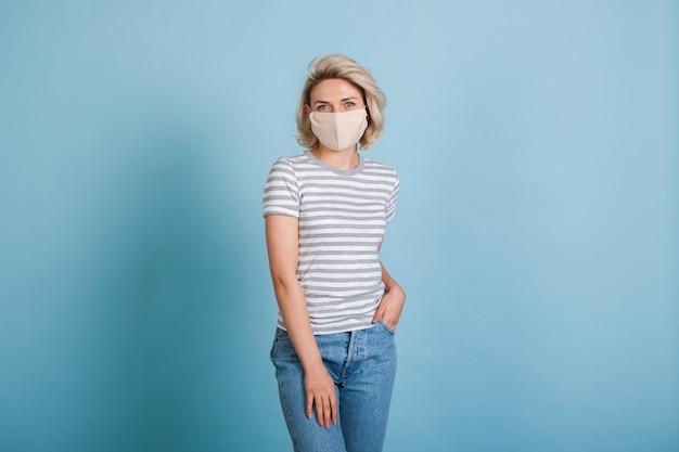 Blondynka z maską medyczną w dżinsach i koszulce pozuje na ścianie w niebieskim studio