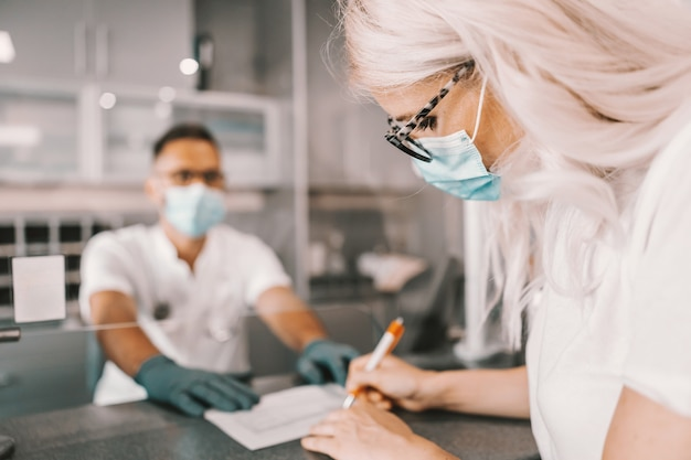 Blondynka z maską siedzi na recepcji i wypełnia formularz do testów na koronawirusa.