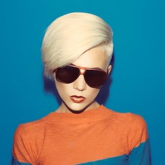 Blondynka z modną fryzurą i okularami przeciwsłonecznymi na niebieskim tle