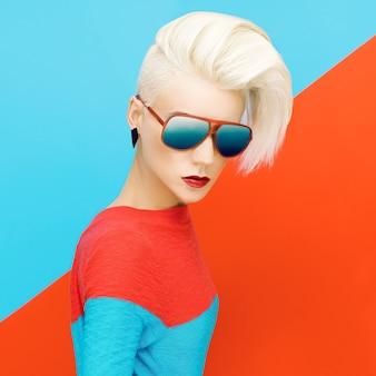 Blondynka z modną fryzurę i sanglasses na jasnym tle. zdjęcie mody
