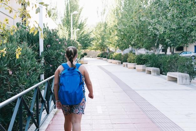Blondynka z niebieskim plecakiem i maską w drodze do szkoły