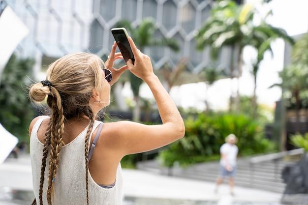 Blondynka z okularami przeciwsłonecznymi, białym podkoszulkiem bez rękawów i warkoczem robi zdjęcie swoim telefonem komórkowym do niektórych nowoczesnych budynków