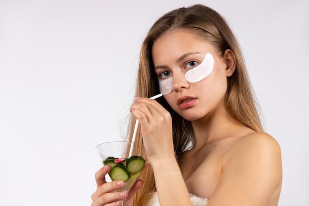 Blondynka z opaskami pod oczami trzymająca detox ogórkowy koktajl zdrowo pielęgnujący biel