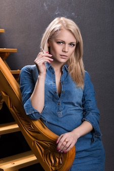 Blondynka z papierosem stoi w pobliżu drewnianych schodów, opierając się o poręcz. strzał studio.