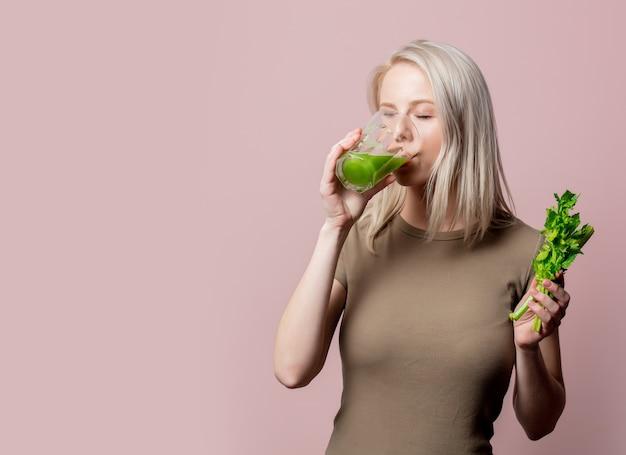 Blondynka z sokiem z selera na różowo