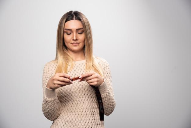Blondynka z uwagą sprawdza zdjęcia na folii polaroid