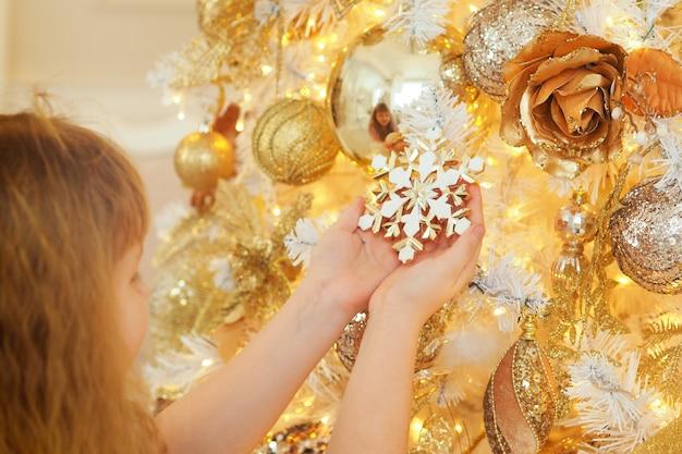 Blondynka z włosami ozdabia choinkę zabawkami i trzyma w rękach świąteczny płatek śniegu