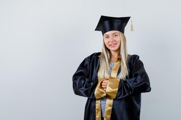 Blondynka zacierając ręce w sukni i czapce ukończenia szkoły i patrząc szczęśliwy.