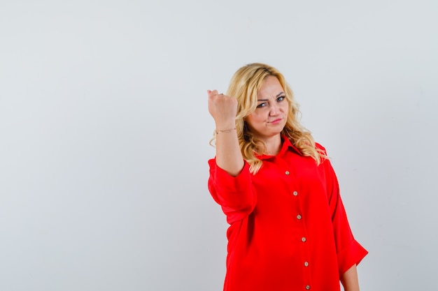Blondynka zaciska pięść w czerwonej bluzce i wygląda ładnie. przedni widok.