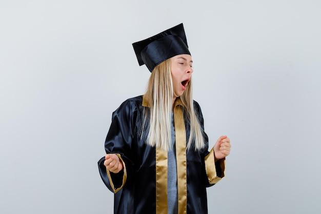 Blondynka zaciska pięści, otwiera usta w sukni i czapce na zakończenie szkoły i wygląda na zaspaną