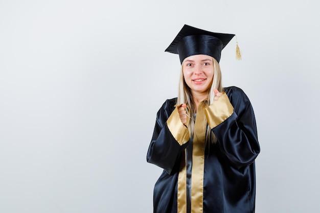 Blondynka zaciskająca pięści w sukni i czapce ukończenia szkoły i wyglądająca na szczęśliwą