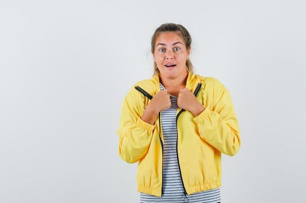 Blondynka zaciskająca pięści w żółtej bomberce i koszuli w paski, wyglądająca na zaskoczoną