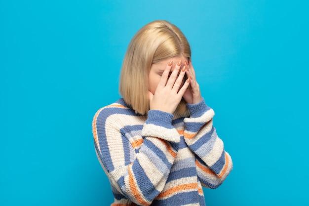Blondynka zakrywająca oczy dłońmi ze smutnym, sfrustrowanym wyrazem rozpaczy, płaczu, widoku z boku