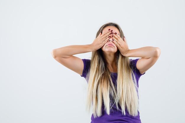 Blondynka zakrywająca oczy rękami w widok z przodu fioletowa koszulka.