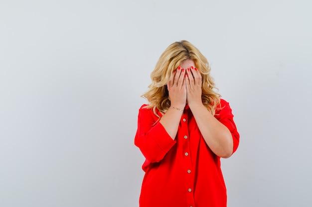 Blondynka zakrywająca twarz rękami w czerwonej bluzce i wyglądająca ponuro. przedni widok.