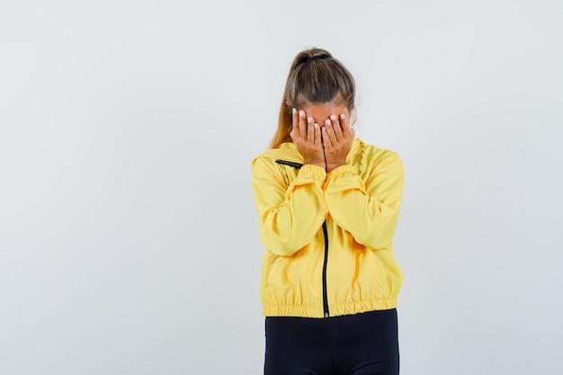 Blondynka zakrywająca twarz rękami w żółtej bomberce i czarnych spodniach i wyglądająca poważnie