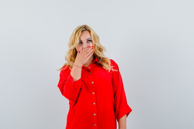 Blondynka zakrywająca usta ręką w czerwonej bluzce i patrząc zaskoczony, widok z przodu.