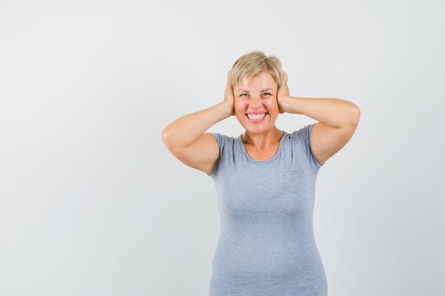 Blondynka zakrywająca uszy dłońmi i uśmiechnięta w jasnoniebieskiej koszulce i patrząc optymistycznie, widok z przodu.