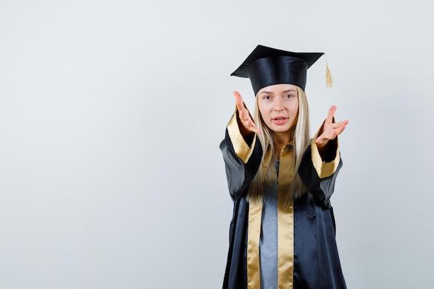 Blondynka zapraszająca w sukni i czapce z okazji ukończenia szkoły i wyglądająca na szczęśliwą