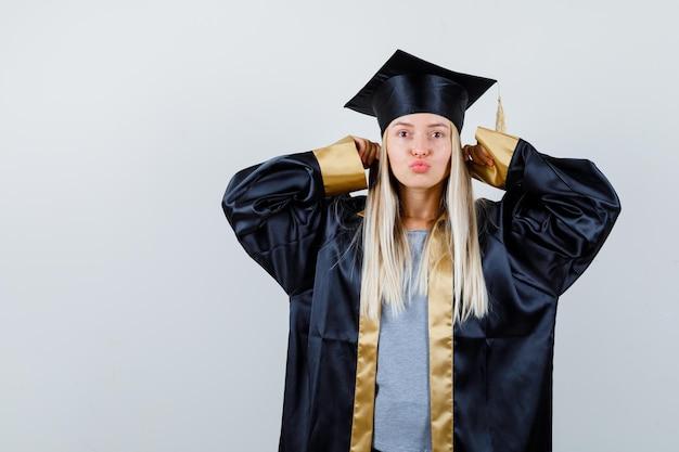 Blondynka zatyka uszy palcami wskazującymi, wysyła buziaki w sukni i czapce na zakończenie szkoły i wygląda na szczęśliwą.