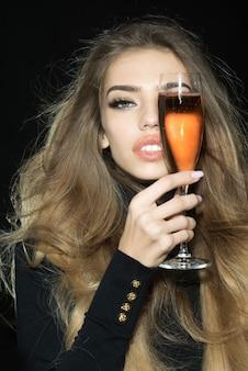 Blondynka ze wspaniałymi włosami trzyma kieliszek szampana. profesjonalny makijaż, seksowne zmysłowe usta, otwarte usta, białe zęby. romantyczna kobieta z długimi zdrowymi włosami zakrywa oko lampką szampana.