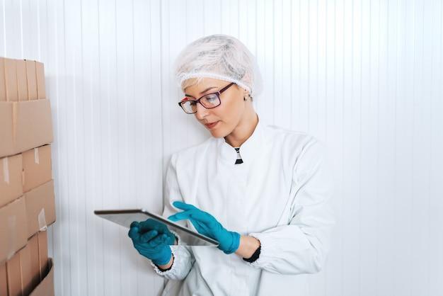 Blondynka żeński pracownik w bezpłodnym mundurze używać pastylkę dla logistycznie podczas gdy stojący obok pudełek w karmowej fabryce.