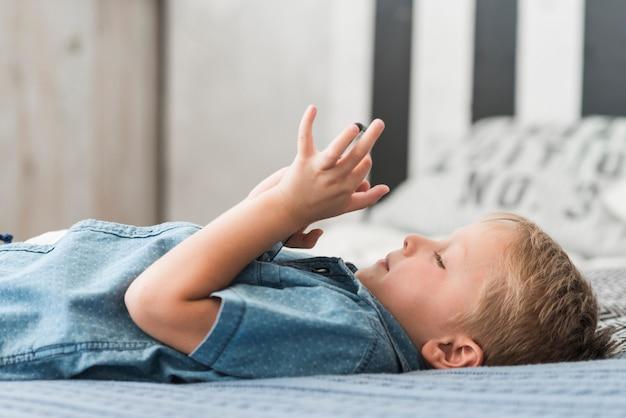 Blondynki chłopiec lying on the beach na łóżkowym używa telefonie komórkowym