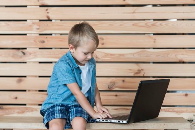 Blondynki chłopiec obsiadanie na stołowym używa laptopie