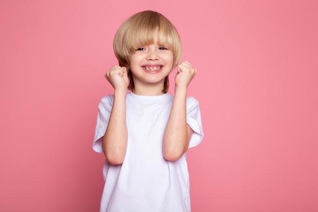 Blondynki chłopiec śliczny śliczny ono uśmiecha się w białej koszulce na menchiach
