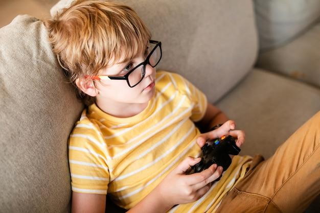 Blondynki chłopiec w dużych szkłach bawić się na konsoli obsiadaniu na leżance. europejskie dziecko posiadające hobby