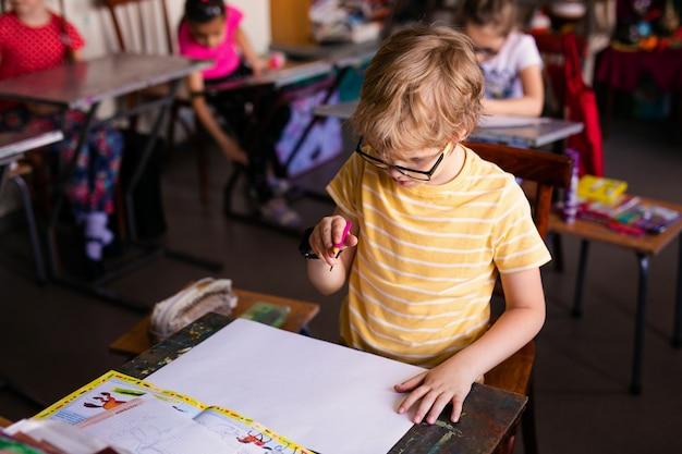 Blondynki chłopiec z szkieł rysować. grupa uczniów szkół podstawowych w klasie na zajęciach plastycznych