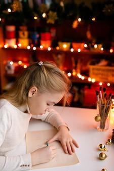 Blondynki dziecka dziewczyny writing list święty mikołaj lub rysować coś na z ciepłym żółtym bokeh
