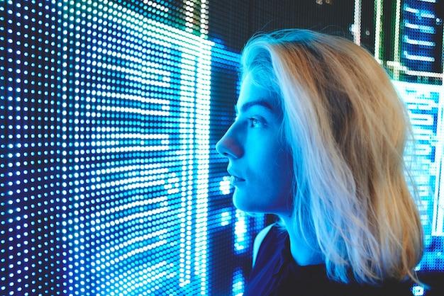 Blondynki dziewczyna na tle neonowi światła, futurystyczny tło